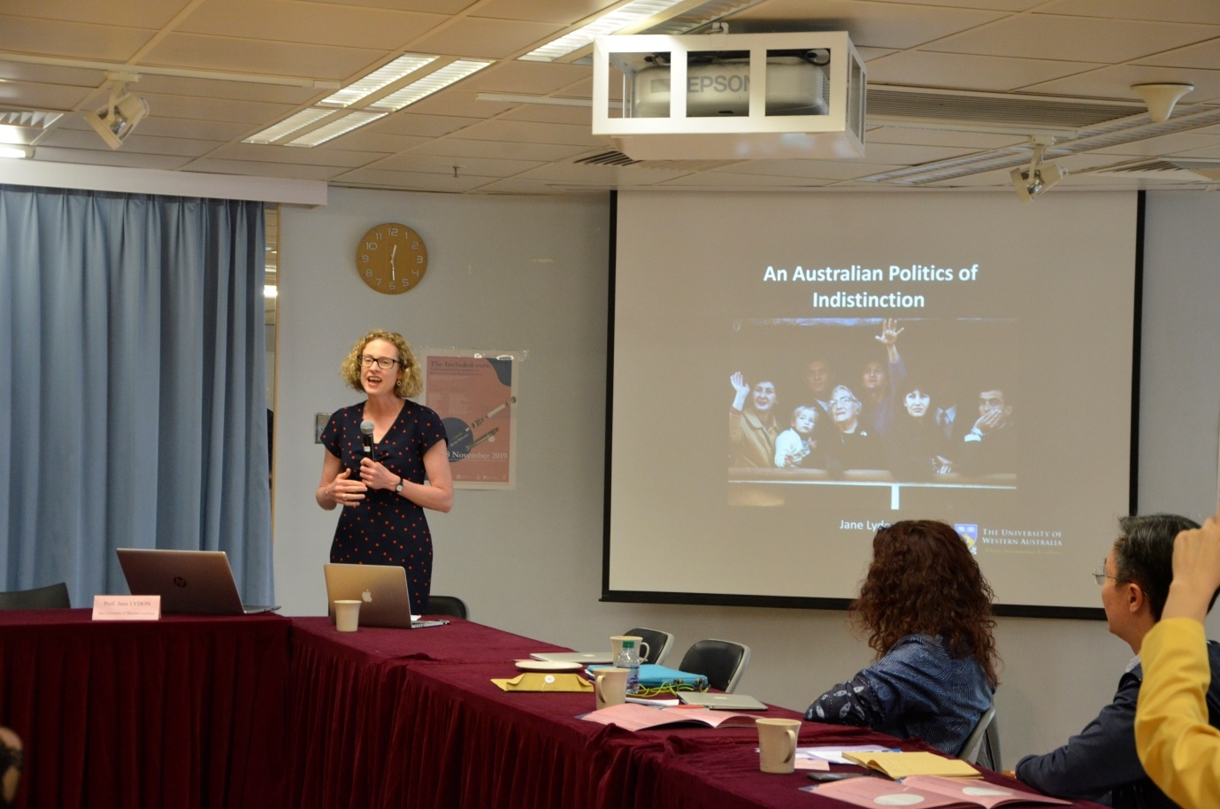 "A woman speaks next to a PowerPoint slide that says ""An Australian Politics of Indistinction""."